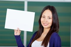 female student displaying white paper - stock photo