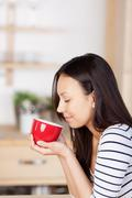 woman enjoying the aroma of coffee at home - stock photo