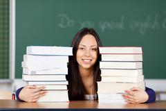 female student looking between stacked books - stock photo