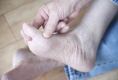 Man rubbing his athletes foot condition Stock Photos
