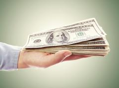 Hand holding pile of cash Stock Photos