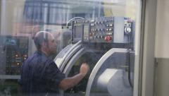 Employee checks a lathe in factory Stock Footage