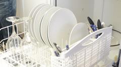 Man loads dishwasher and walks away Stock Footage