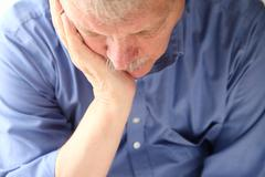 older man slumped in depression - stock photo