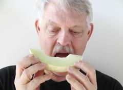 Older man eating melon slice Stock Photos