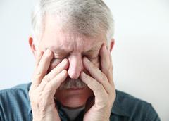 senior suffering from sinus pressure - stock photo