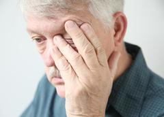 Tired man rubbing his eye Stock Photos