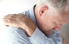 Senior reaches to scratch his back Stock Photos