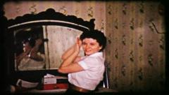 199 woman combs hair in front of mirror - vintage film home movie Stock Footage
