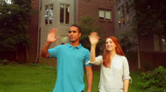 interracial couple waving at neighbors wave - stock footage