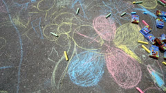Chalks boxes lay near childish drawing on asphalt surface Stock Footage
