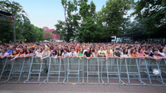 Crowd of music fans applaud beyond fence at concert of Chaif - stock footage