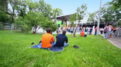 Fans sit on grass and stand near stage at concert of Chaif band Stock Footage