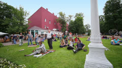 People dance and rest on grassplot at concert of Chaif band Stock Footage
