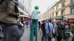 Man in costume walks on stilts among crowd at street Stock Footage