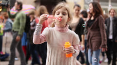 Little girl inflates soap bubbles among people which walk Stock Footage
