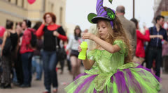 Little girl in elf costume inflates soap bubbles Stock Footage