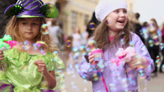Little girl inflate lot of soap bubbles in street Stock Footage