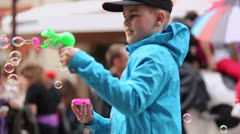 Young boy inflates soap bubbles among people which walk Stock Footage