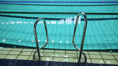 Handrails at border of swimming pool with wavy water Stock Footage