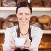 Worker serving coffee in a bakery Stock Photos