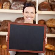 Bakery worker holding a blank chalkboard Stock Photos