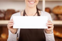 Bakery worker holding up a blank sign Stock Photos