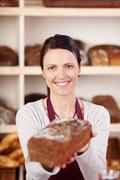 Smiling bakery worker with bread Stock Photos