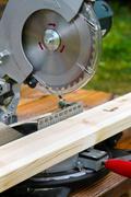 portable circular saw and wood plank - stock photo