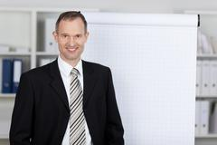 smiling businessman with flipchart - stock photo