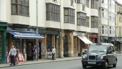 Taxi drives along oxford high street, england Stock Footage