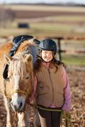 young girl leading horse to stable - stock photo