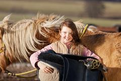 portrait of a young girl carrying a saddle - stock photo