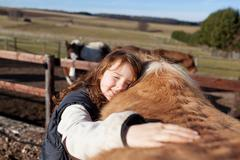 Young girl petting her horse Stock Photos