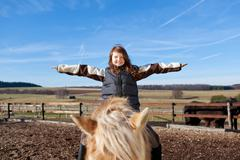 happy girl playing on top of her horse - stock photo