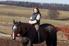 Portrait of a young girl riding her dark bay horse Stock Photos