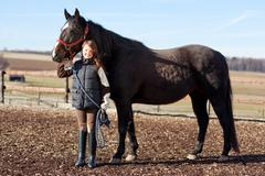 portrait of a pretty young girl with her horse - stock photo