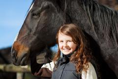 portrait of a proud young girl with her horse - stock photo