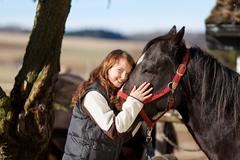 smiling young girl with a dark bay horse - stock photo