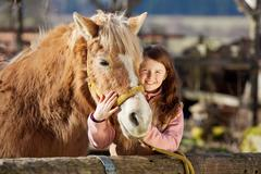 Happy little girl cuddling her horse Stock Photos