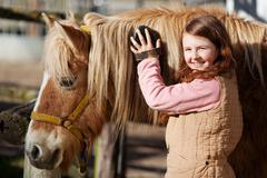 smiling teenager grooming her horse - stock photo