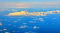 Aerial view of mountains and clouds on top Stock Photos