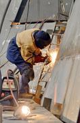 Worker grinding metal inside of shipyard Stock Photos