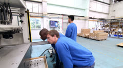 Time lapse of male workers in a factory operating machinery Stock Footage