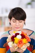 woman smelling a bunch of roses - stock photo
