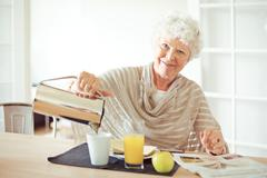 Cheerful grandma at home having breakfast Stock Photos