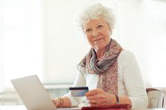 mature lady with credit card shopping online - stock photo