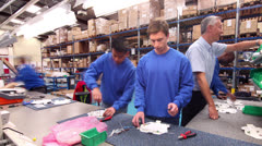 Time lapse of male workers in a factory assembling electrical fittings Stock Footage