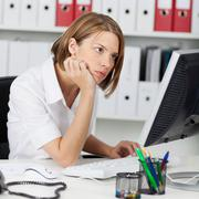 office worker reading her monitor - stock photo