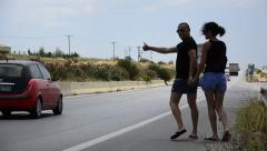 Couple hitchhikers hitch hiking and try to stop a vehicle Stock Footage